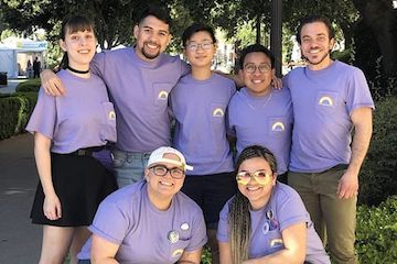 Group photo of the LGBT undergraduate and graduate student interns wearing purple shirts with a rainbow on the breast pocket